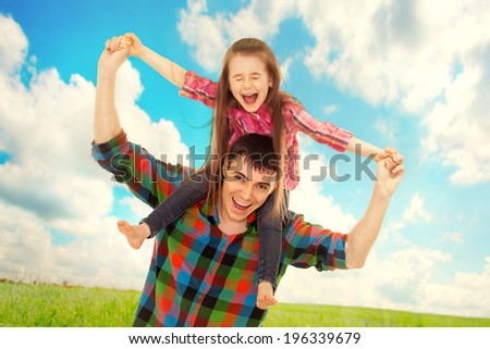 Joyful father with daughter on shoulders carefree and happy. Fathers day, family holiday, vacation - stock photo