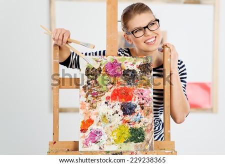 Joyful female artist in eyeglasses holding paintbrushes in her working studio. Happy smiling woman painter standing behind wooden easel.    - stock photo