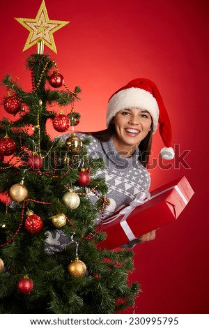 Joyful female in Santa cap looking at camera out of decorated xmas tree - stock photo