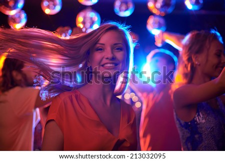Joyful female looking at camera while dancing in night club with her friends on background - stock photo