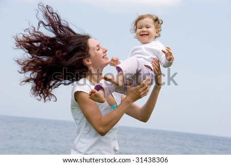 Joyful female playing with adorable infant on fresh air at summer