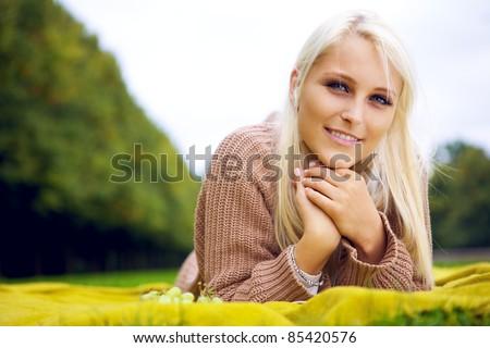 Joyful female relaxing on a blanket - stock photo