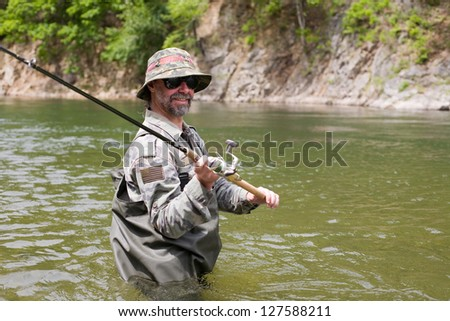 Joyful Fisherman catches of salmon in a mountain river. - stock photo