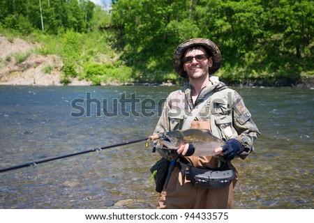 Joyful fisherman keeps caught masu salmon (or cherry salmon). Russia. Primorskiy  kray. - stock photo