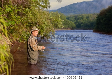 Joyful fisherman on a mountain river catches of salmon (pink salmon). Far East Russia.