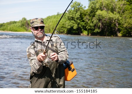 Joyful fisherman pulls caught salmon from the river. - stock photo
