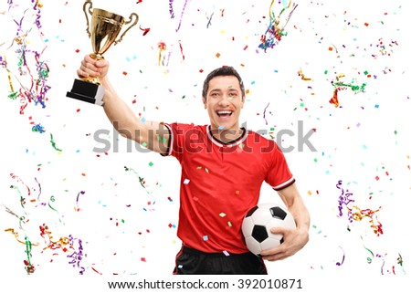 Joyful football player holding a gold trophy and celebrating with confetti streamers around him isolated on white background - stock photo