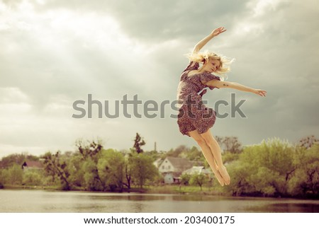 joyful freedom: portrait of beautiful blond dancing young woman with falling sun light rays from blue sky at river or water lake on spring or summer nature green outdoors background copy space picture - stock photo