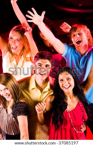 Joyful friends enjoying themselves at discotheque in night club