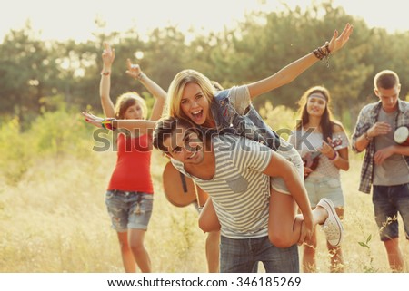 Joyful friends relaxing, a girl on guy's back in the forest outdoors - stock photo
