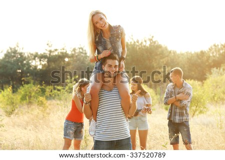 Joyful friends relaxing, a girl on guy's shoulders in the forest outdoors - stock photo