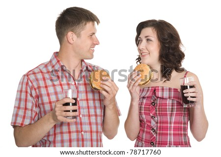 Joyful girl and a guy eating hamburgers and drinking a refreshing drink.