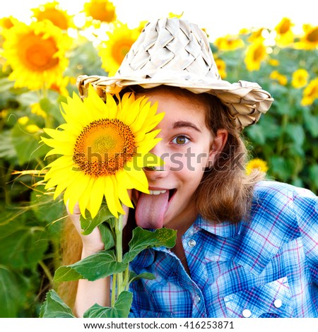Joyful girl in blue plaid shirt with sunflowers in a wicker hat showing tongue on a field - stock photo