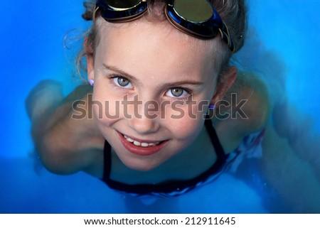 Joyful girl in water with swimming goggles - stock photo