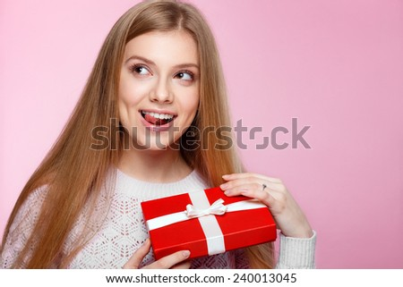 Joyful girl in white sweater with a red gift box on the pink background, Valentines Day, holidays, happiness, International Women's Day - stock photo