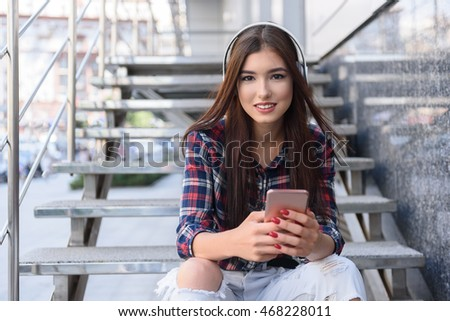 Joyful girl listening to melody from smartphone