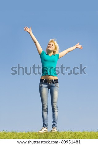 Joyful girl on a background of grass and sky - stock photo