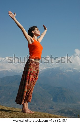 Joyful girl over the mountains with outstretched arms. Early in the morning. - stock photo