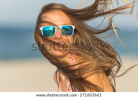 Joyful girl  playing and having fun in sunny tropical destination for travel holiday. shallow DOF, focus on woman's lips, sunglasses, motion - stock photo