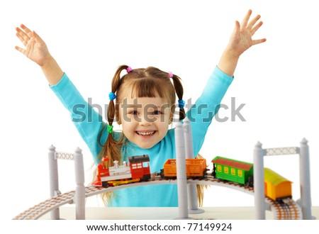 Joyful girl playing with toy railway - stock photo