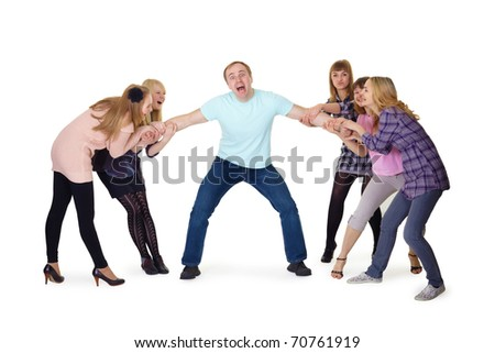 joyful girl pulled a man confused by the arms in opposite directions - stock photo