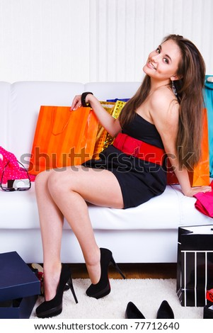 Joyful girl sitting on the sofa with lots of shopping bags and boxes