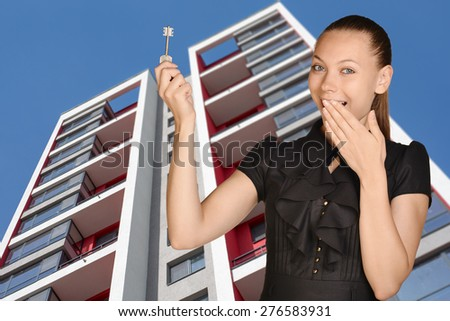 Joyful girl standing on background of building and is holding keys. - stock photo