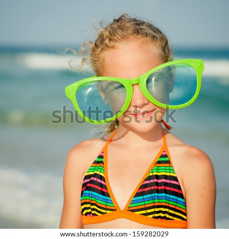 joyful girl with big sunglasses on the beach