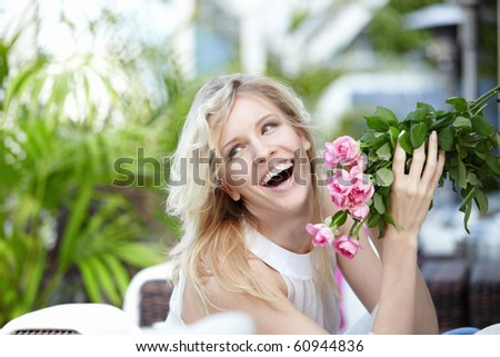 Joyful girl with flowers in a cafe - stock photo