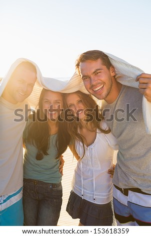 Joyful group of friends having fun together on the beach - stock photo