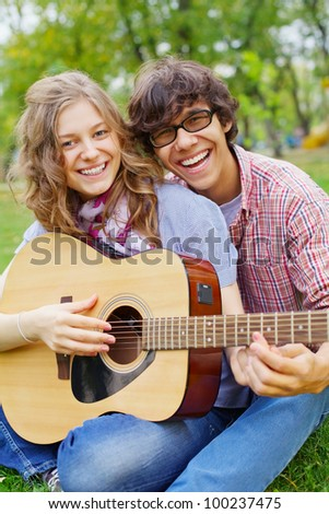 Joyful guy teaching beautiful teenage girl play guitar in summer park - stock photo