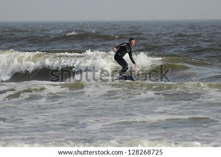 Joyful, happy surfer riding a wave - stock photo