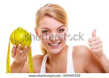 Joyful happy woman girl holds holding grapefruit and measurement tape with thumb up. Fitness and healthy lifestyle concept. Dieting and slimming. Isolated on white background. - stock photo