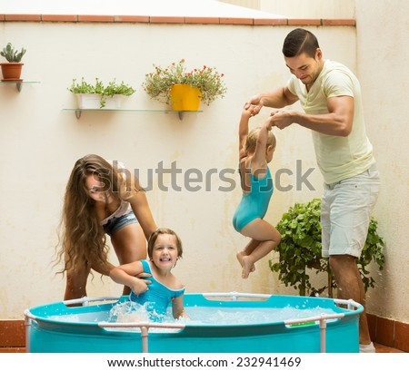 Joyful happy young family with kids playing in pool at terrace. Focus on man  - stock photo