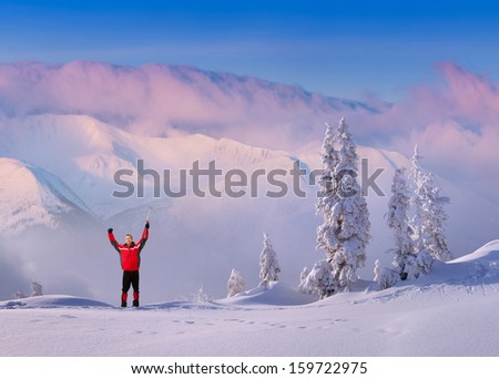 Joyful hiker meets a morning in the snowy mountains - stock photo