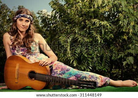 Joyful hippie girl playing the guitar outdoor in the sunny summer day. Child of nature. Lifestyle.   - stock photo
