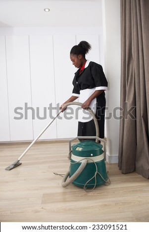 Joyful house cleaner cleaning clean room vacuum cleaner - stock photo