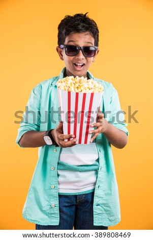 Joyful indian kid holding a big box of popcorn and looking at the camera isolated on yellow background, Portrait of adorable indian young boy eating popcorn, asian kid and popcorn