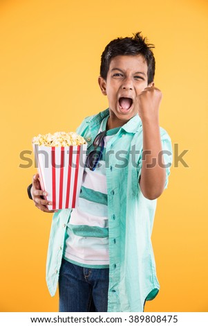 Joyful indian kid holding a big box of popcorn and looking at the camera isolated on yellow background, Portrait of adorable indian young boy eating popcorn, asian kid and popcorn - stock photo