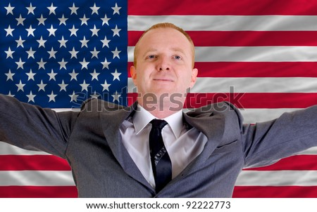 joyful investor spreading arms after good business investment in america, in front of flag