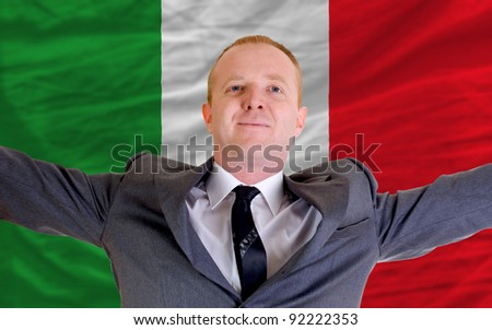 joyful investor spreading arms after good business investment in italy, in front of flag