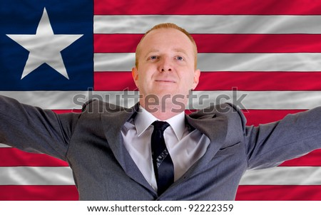 joyful investor spreading arms after good business investment in liberia, in front of flag