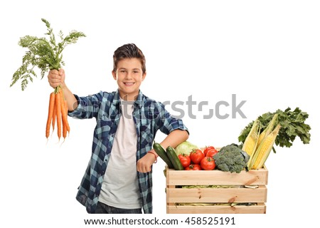 Joyful kid holding a bunch of carrots and posing next to a crate full of vegetables isolated on white background - stock photo