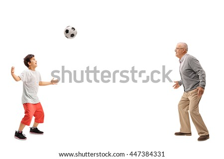 Joyful kid playing soccer with his grandfather isolated on white background