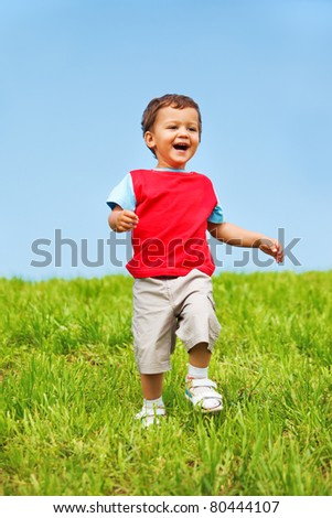 Joyful kid running down the green hill - stock photo