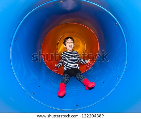 Joyful kid sliding in tube slide on playground - stock photo