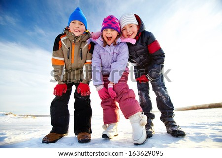 Joyful kids in winterwear looking at camera while having happy time outside - stock photo