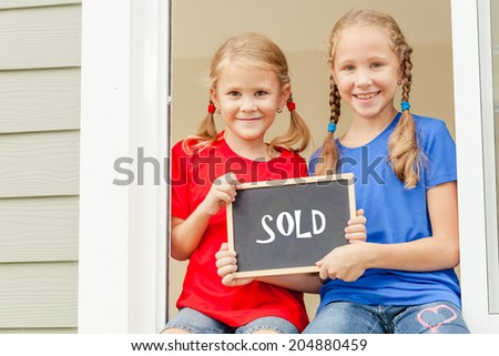 "Joyful kids looking out the window at home and  holding a sign saying ""sold"" - stock photo"