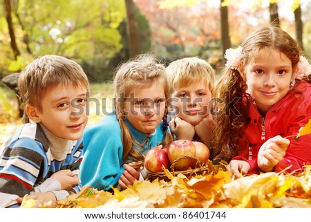 Joyful kids lying on autumnal leaves around apple basket