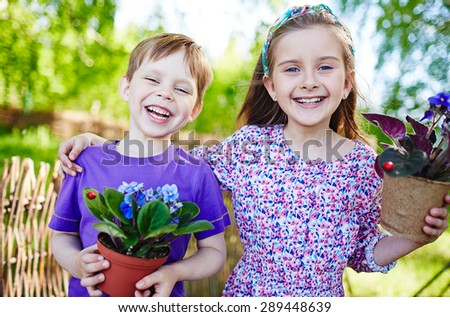 Joyful kids with garden violets looking at camera